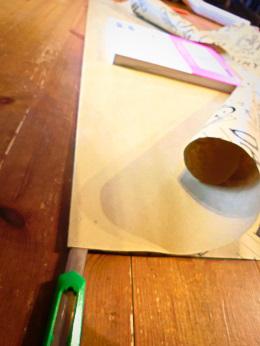 本の上の部分の大きさを確認して包装紙をカッターで切ります
